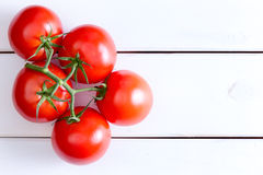 Five Hydroponic tomatoes over white wooden table. Top down view on five medium Hydroponic red tomatoes on stem with copy space over white painted wooden table royalty free stock photos