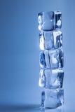 Five Ice cubes on blue background studio shot photo Royalty Free Stock Image