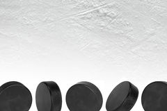 Five Ice Hockey Pucks. Washers on the ice of the hockey field. Texture, background, concept Royalty Free Stock Photos