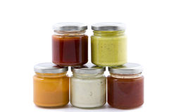 Five jars filled with various sauces royalty free stock photos