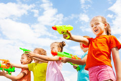 Five kids play with water guns. Against sky on the background Royalty Free Stock Image