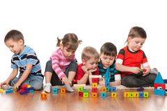 Five kids playing on the floor. Five kids are playing on the floor with blocks in kindergarten stock image