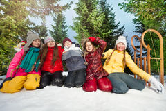 Five kids playing in the snow at wintertime Royalty Free Stock Photos