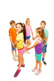 Five kids roundelay in a circle isolated on white. Five kids standing in a circle roundelay and holding each other hands Royalty Free Stock Photography