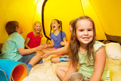 Five kids sit inside a yellow tent Royalty Free Stock Images