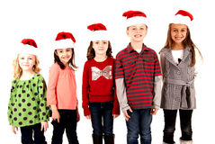 Five kids standing wearing santa hats smiling Stock Images