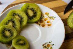 Five kiwi fruit slices on a white table. Wooden base. Fresh fruits prepared for a fruit salad Stock Image