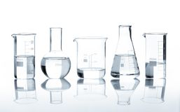 Five laboratory flasks with a clear liquid Royalty Free Stock Photo