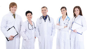Five laughing successful doctors standing together. Group of five laughing successful doctors standing together and looking at camera royalty free stock photos