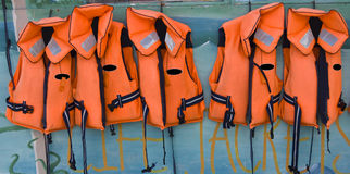 Five life jackets in a row. Row of five orange life jackets hanging outside a yacht club Stock Photo
