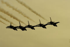 Five in a line. 5 F16 Thunderbirds flying in a tight formation with smoke tails Royalty Free Stock Image