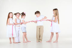 Five little children draw over pink rope. Five strained little children in white clothes draw over pink rope Royalty Free Stock Image