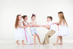 Five little children draw over pink rope. Five happy little children in white clothes draw over pink rope Royalty Free Stock Images