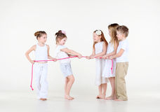 Five little children in white clothes draw over rope. Five cute little children in white clothes draw over pink rope Royalty Free Stock Photos