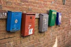 Five mailboxes hang on a brick wall stock image