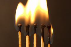 Five matches - fire. Five matches on dark background - burning (setmatches royalty free stock photography