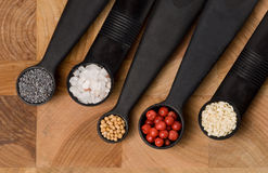 Five measuring spoons with spices. Five measuring spoons on a cutting board with various spices Stock Photos