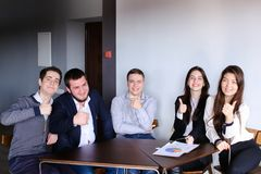 Managers of two men and woman possing in camera and smilling bro. Five members of board of directors, two girls and three guys sit at table in modern office Royalty Free Stock Photo