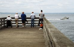 Five Men Fishing on a Pier. Five men fishing off a pier on Long Island Sound in Glen Cove, NY with a boat passing by Stock Photography