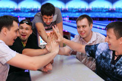 Five men sit at table and touch hands in bowling Royalty Free Stock Photography