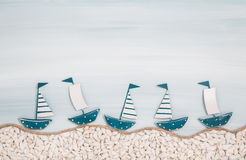 Five metal handmade sailboats on a blue ocean background for sum Stock Images