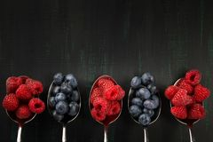 Five metal spoons with raspberries and blueberries, lie on a dark background. Five metal spoons with  raspberries and blueberries, lie on a dark background Stock Image