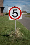 Five miles per hour sign. A five miles per hour sign on a grass verge Stock Image