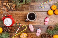 Five minutes before the New Year and a cup of coffee. Cozy wooden background Christmas sweets and toys pigs. Place under your text royalty free stock photography