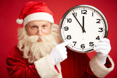 Five minutes to Christmas. Happy Santa in eyeglasses pointing at clock showing five minutes to Christmas royalty free stock photo