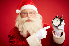 Five minutes to midnight. Happy Santa pointing at clock showing five minutes to midnight on red background stock image
