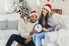 Five minutes to New Year midnight. Five minutes to New Year. Multiethnic couple holding clock, copy space stock images