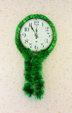 Five minutes to twelve on old wall clock decorated with green tinsel Royalty Free Stock Photos