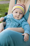 Five month old serious baby sitting on mother knee Stock Image