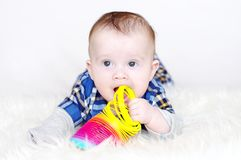 Five-months baby plays a multi-colored spring Royalty Free Stock Images