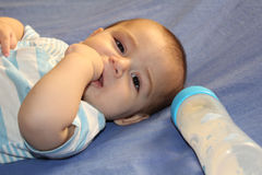 Five months old baby boy playing on the bed Stock Images