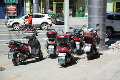 Five motorbikes parked on side of street in city Stock Images