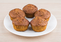 Five muffins in glass plate on table Stock Photos