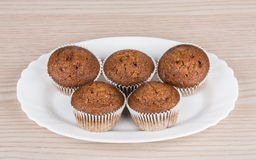 Five muffins in glass plate on table Stock Images