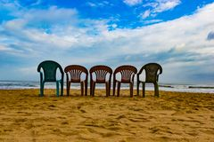 Five multi cloured chair on a sandy beach with blue sky in a sunny day perfect holiday destination Royalty Free Stock Photography