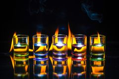 Five multicolored full of drinks shot glasses reflected on the g royalty free stock photos