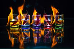 Five multicolored shot glasses full of drink and with the red ch. Ili peppers lying inside them behind which the flame burns on a black background. Conceptual royalty free stock image