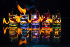 Five multicolored shot glasses full of drink and with the red ch. Ili peppers lying inside them behind which the flame burns on a black background. Conceptual royalty free stock images