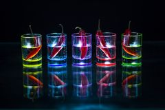 Five multicolored shot glasses full of drink and with the red ch. Ili peppers lying inside them symmetrically placed a black background. Conceptual, commercial royalty free stock photography