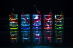 Five multicolored shot glasses full of drink and with the red ch. Ili peppers lying inside them symmetrically placed a black background. Conceptual, commercial stock photo