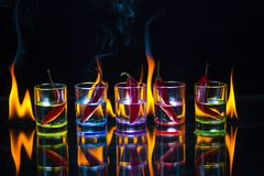 Five multicolored shot glasses full of drink and with the red ch. Ili peppers lying inside them behind which the flame burns on a black background. Conceptual stock image