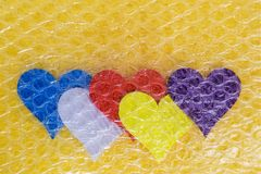Five multicolored valentine hearts are packed with a transparent bubble wrap on a yellow background. Concept fragility of love royalty free stock image