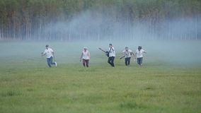 Five musicians with instruments running through a smoke-filled field. Very cool cheerful frame. Overall plan in slow motion stock video footage