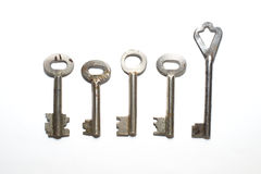 Five old keys to the safe on a white background Stock Photography
