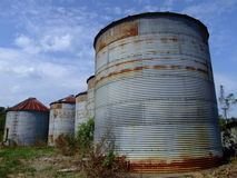 Five Old,Rusty Empty Silos. Five rusty, abandoned, grain-storage silos in farm country Stock Images
