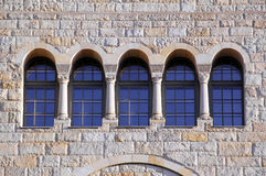 Five old windows with arches, columns and lattices on a stone wa Royalty Free Stock Image